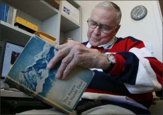 "Robert Schaller, a former pediatric surgeon who still teaches at Children's Hospital and Regional Medical Center in Seattle, looks over a copy of ""The Ascent of Nanda Devi."" In 1965, Schaller tried to scale the peak to install a listening device that never made it to the top. (Photo Credit: Grant M. Haller/Seattle Post-Intelligencer / SL)"